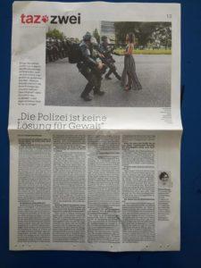 Bild von einer Tageszeitung Seite von der taz. Oben ist ein Bild von einer Schwarzen Frau im Kleid, die bei einer Protest auf der Strasse steht, ganz ruhig und selbstbehauptend, und drei Bullen in schwarzen Kampfausrüstung rennen ihr entgegen, um sie festzunehmen