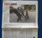 Bild von einer Tageszeitung Seite von der taz. Oben ist ein Bild von einer jungen Schwarzen Frau im Kleid, die bei einer Protest auf der Strasse steht, ganz ruhig und selbstbehauptend, und drei Bullen in schwarzen Kampfausrüstung rennen ihr entgegen, um sie festzunehmen