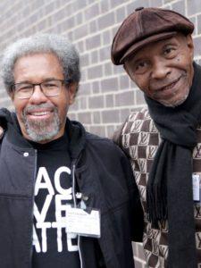 Ein Foto von Albert Woodfox und Robert King, zwei ältere Schwarze Männer lächeln im Bild